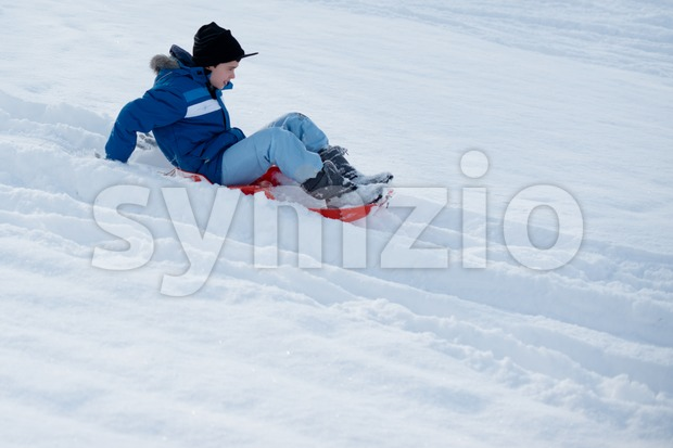 Stuttgart, Germany – February 9, 2013: A boy having fun with his sledge, bright and white winter scene on February ...
