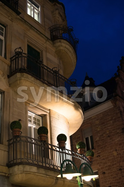 Facade of a beautiful building with balconies and plastic flowers in the evening in Heidelberg, Germany