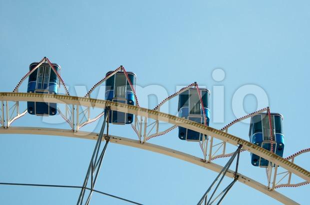 Ferris wheel at amusement park against great blue sky