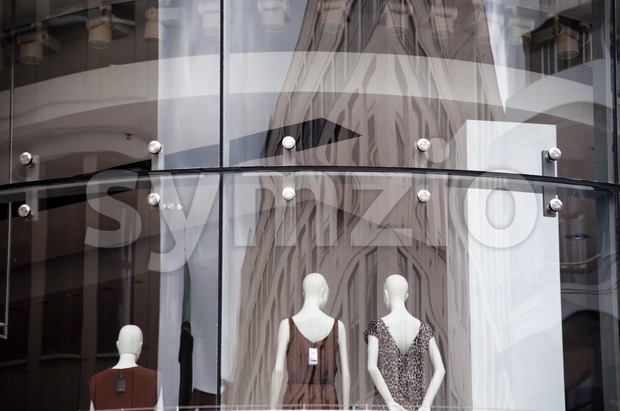 Modern boutique window with dressed mannequins as seen from outside