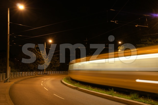 Night view of a main road with blurry movement of a tram